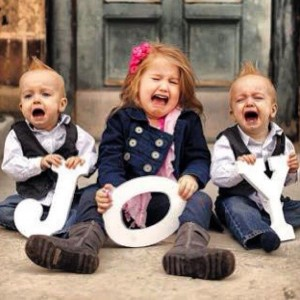 Three children dressed for Christmas crying.