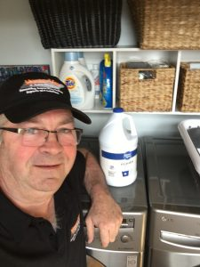 Volunteer Mold Inspector Bob poses in a laundry room in front of Chlorine Bleach container.