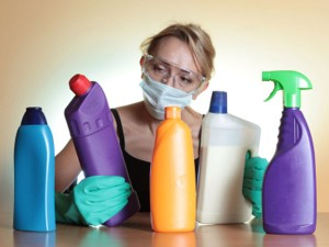Housewife wearing a face mask looking at household chemicals used to clean.