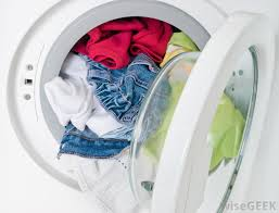 Photo of a slightly ajar laundry machine full of laundry.