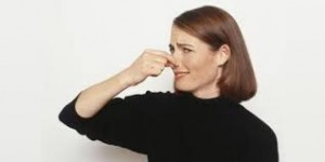 Photo of a woman holing her nose due to an offending mold odor.