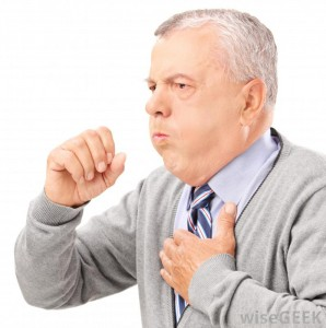 Middle aged man holding his chest and coughing with his hand in front of his mouth.
